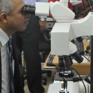 Kirkuk provincial judge Mohan Abrahim sits down at a ballistic stereoscopic microscope at the Criminal Evidence Unit forensics laboratory in Kirkuk City, Iraq, July 5, 2011. The ballistic stereoscopic microscope allows forensic investigators and experts to match up an expended bullet casing to the weapon that fired it by analyzing the casing with test-fire casings. (U.S. Army photo by Sgt. David Strayer/Released)